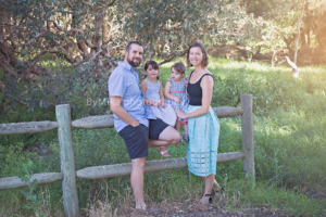 Family of four in blue tones captured on fence ByMika family photographer