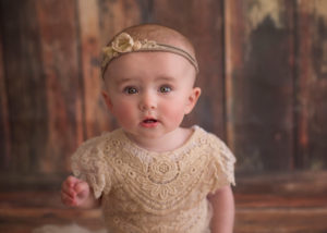 ^ month old baby sitting on wooden backdrop