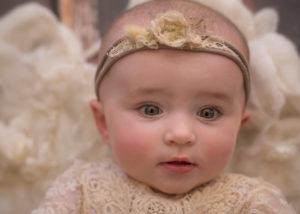 Baby girl on floor rug looking in camera
