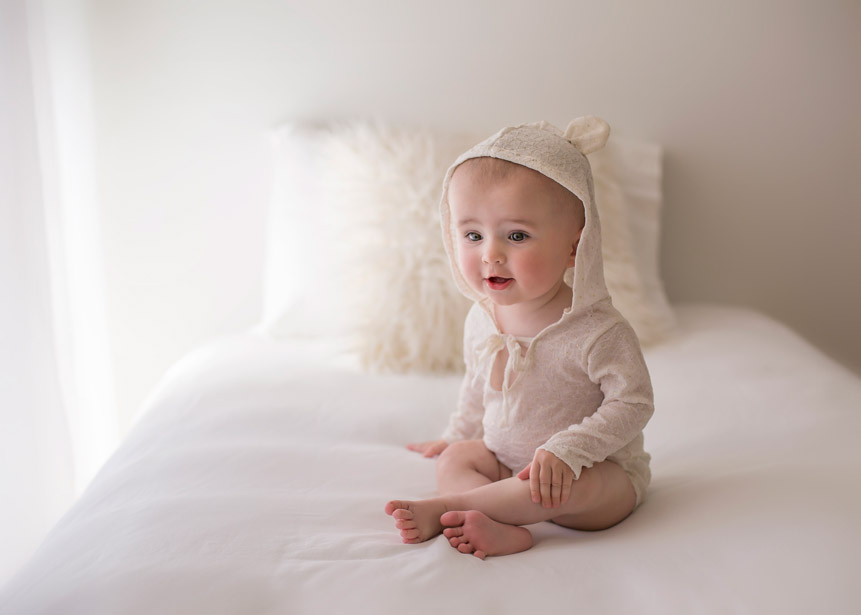 Baby Ella on bed with bear romper