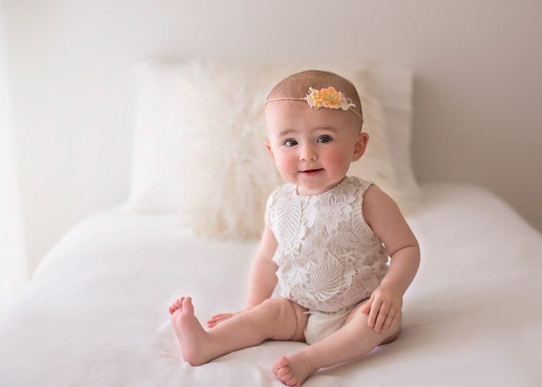 Baby Ella sitting on bed posing for camera